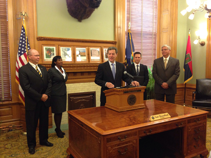 Governor Brownback stands Chairman Wilk and new appointees, Newton, Bain, and Feuerborn